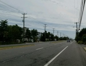 In this photo from another community, the new two deck poles appear on the left side of the street while the older poles are on the right side. This is a depiction of the new distribution poles planned for the east side of Dune Drive in the project area.